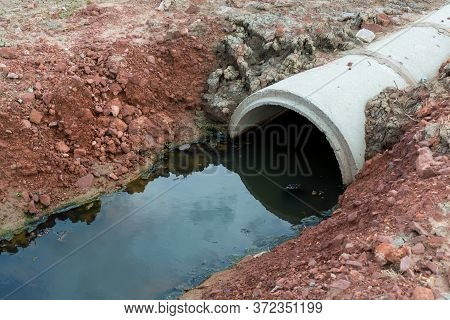 Concrete Circular Run-off Pipe Discharging Water. Sewage Pipe Polluting The River. Sewage Or Domesti
