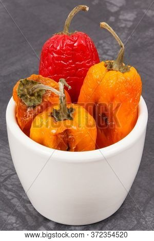 Moldy And Wrinkled Peppers In White Bowl. Concept Of Unhealthy, Decompose, Spoiled Vegetable