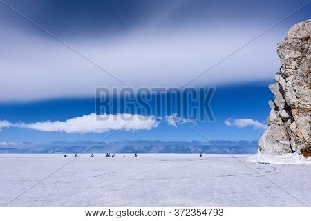 Group Of People Rides Bicycle On The Frozen Lake Baikal Near Cape Burkhan In Sunny Weather With Beau