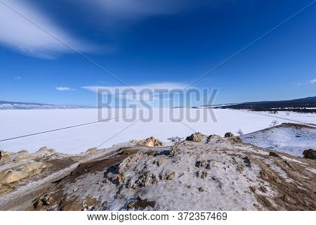 View To Sarai Beach From Cape Burhan On Olkhon Island On Sunny Winter Day. Frozen Lake Baikal Covere