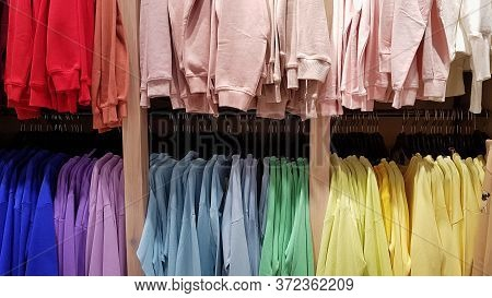 Bright Colorful Sweatshirts Hanging At A Fashion Store. Closeup Of Multi-colored Yellow, Red, Pink,