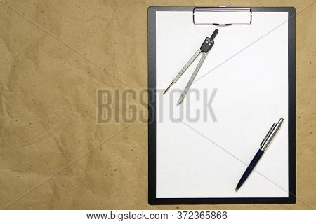A Tablet With A White Sheet Of A4 Format On A Beige Craft Paper With Pen And Divider. Concept Of Acc