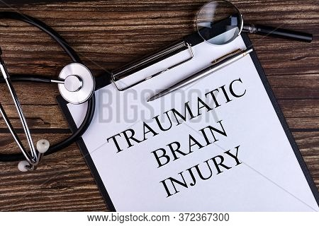 Traumatic Brain Injury Text Is Written On A Tablet Lying On A Dark Table With A Stethoscope And A Ma