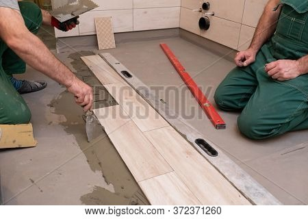Rubber Hammer. An Experienced Construction Worker. Laying Terracotta In The Bathroom. Work Clothes.