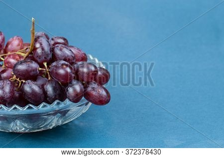 Purple Table Vine Grapes In A Vintage Glass Bowl On Blue Background