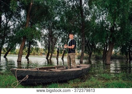 Fisherman Is Sitting In The Old, Wooden Rowboat And Catching The Fish On Sunny Day.