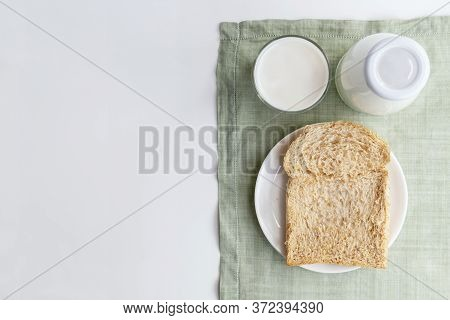 A Bottle Of Milk And Glass Of Milk With Sliced Bread On Dish On Green Cloth On White Background. Hea