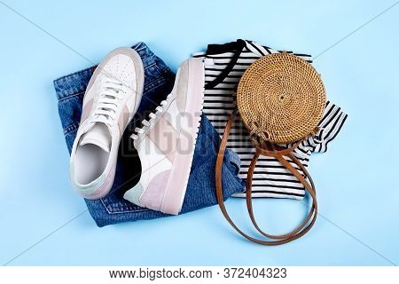 Blue Jeans Shorts, Sneakers, Striped Shirt And Rattan Bag On Blue Background. Overhead View Of Summe