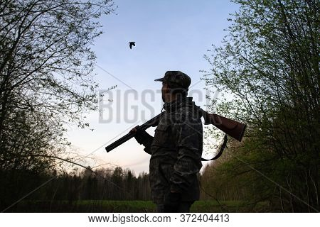 A Hunter With An Unloaded Shotgun On His Shoulder Stands In The Dusk In A Forest Clearing And Sees A