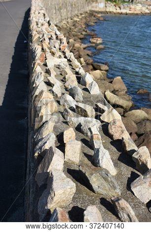 Jagged Adn Rough Stone Retaining Wall Along The Coastline.