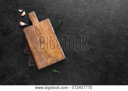 Empty Wooden Cutting Board On Black Stone Kitchen Table, Top View, Flat Lay. Wooden Platter, Copy Sp
