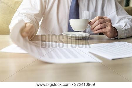Businessman Analyzing Accounting Financial Documents With Cup Of Coffe In Hands. Man Holding Documen