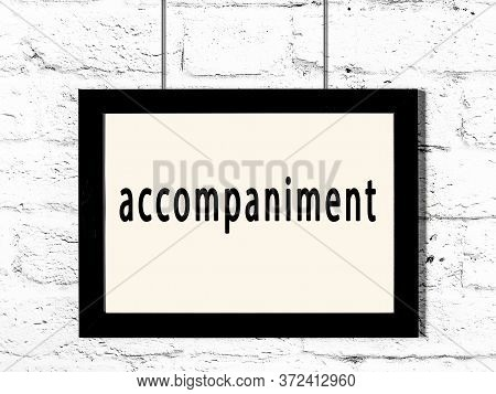 Black Wooden Frame With Inscription Accompaniment Hanging On White Brick Wall