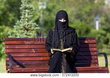 A Migrant From The Middle East Is Sitting On A Bench. Arab Woman In Black National Dress Is Reading