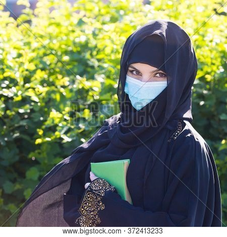 Oriental Woman In A Protective Medical Mask Quaran In Her Hands. A Migrant From The Middle East In A