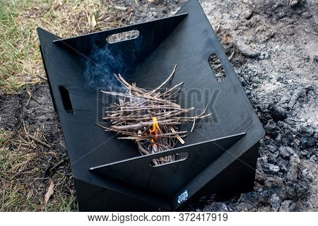 Starting The Camp Fire With Kindling In A Portable Foldable Firepit