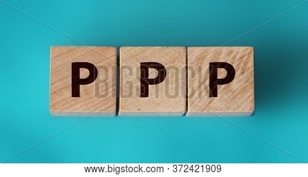 Three Wooden Cubes With Letters Ppp On Aquamarine Cyan Board. Business Concept