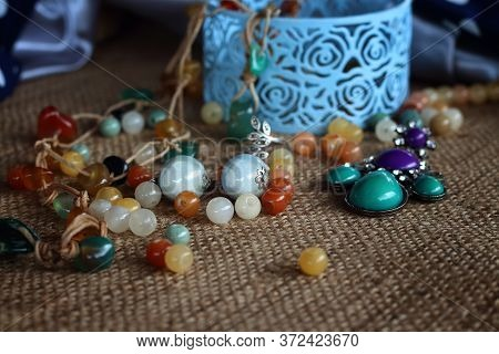 Jewelry In A Box. Jewelry Bead, Earrings Chains On A Sack Background. Design, Fashion And Style Of J