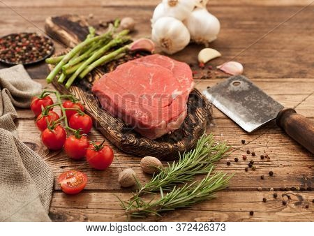 Fresh Raw Barbeque Braising Beef Steak On Chopping Board With Asparagus And Garlic With Cherry Tomat