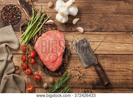 Beef Fresh Braising Steak On Chopping Board With Garlic, Asparagus And Tomatoes With Salt And Pepper