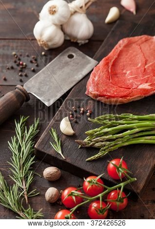 Beef Braising Steak, Fresh Raw Slice On Chopping Board With Garlic, Asparagus And Tomatoes With Salt