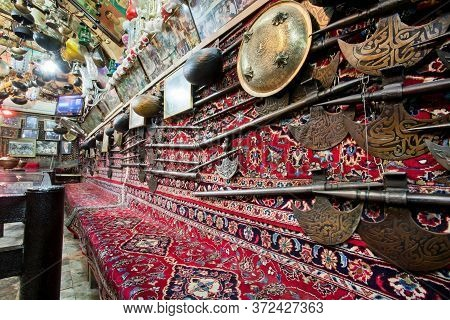 Isfahan, Iran: Interior Of Historical Persian Tea House With Old Carpets, Vintage Weapon, Antiques O
