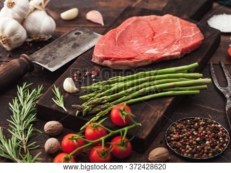 Slice Of Fresh Raw Barbeque Braising Beef Steak On Chopping Board With Asparagus And Garlic With Tom