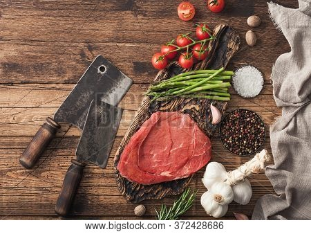 Braising Steak On Chopping Board With Rosemary, Asparagus And Tomatoes With Salt And Pepper With Ros