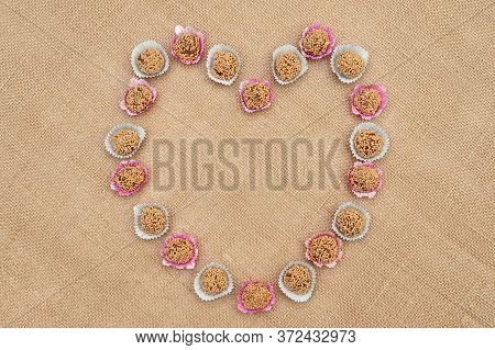 Traditional Brazilian candy called Brigadeiro de Amendoim in Brazilian Portuguese. Made with crushed peanuts, margarine and condensed milk. Top view. Heart shape. Copy space. Jute fabric background.