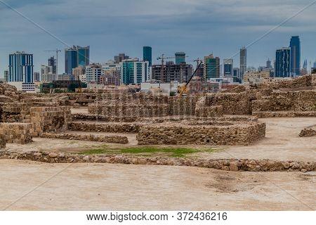 Ruins Of Bahrain Fort Qalat Al-bahrain And Manama Skyline In Bahrain