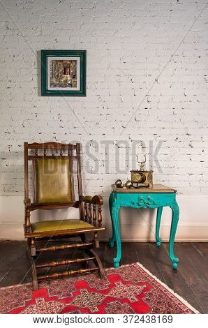 Classical Wooden Rocking Chair, Antique Golden Telephone Set On Top Of Green Wooden Vintage Table An