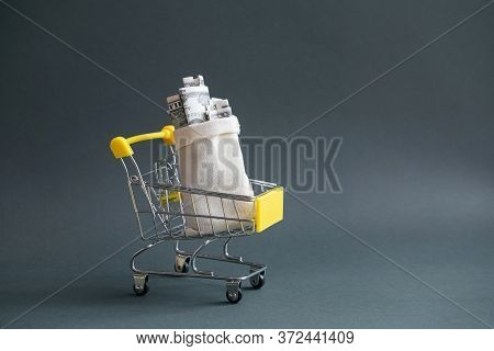 A Yellow Shopping Cart With A Canvas Bag Filled With Money On A Dark Isolated Background. Close-up,