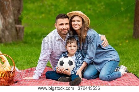 Loving Parents And Their Cute Son With Soccer Ball Sitting On Picnic Blanket At Park, Panorama