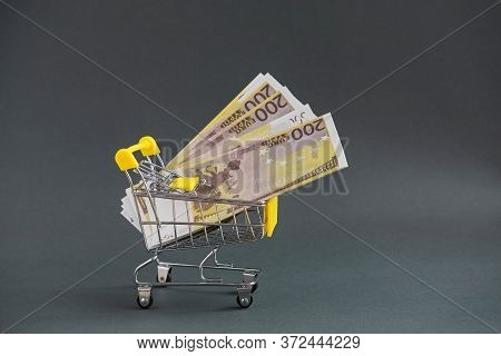 A Yellow Shopping Cart With A Wad Of Euro Money On A Dark Isolated Background. Close-up, Copy Of The