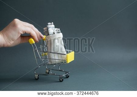 A Womans Hand Holds A Yellow Shopping Cart With A Canvas Bag Filled With Money On A Dark Isolated Ba