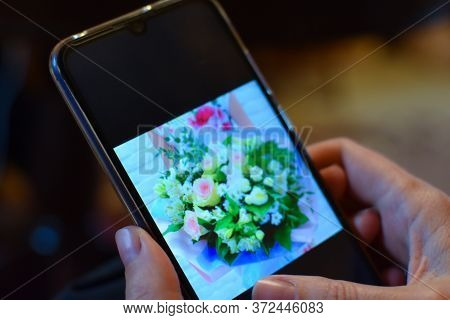 Choosing A Bouquet Of Flowers In The Online Catalog On The Phone. A Woman Buys Flowers In An Online