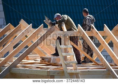 Moscow. Russia. May 2020. The Builders Working On Roof Of Wooden House. Men Building A Wooden House.