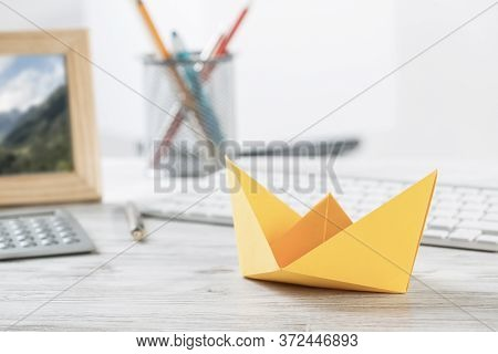 Businessman Workspace With Office Wooden Desk And Yellow Paper Ship. Flat Lay Table With Calculator