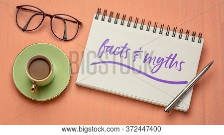 acts and myths note - handwriting in a spiral notebook with coffee and reading glasses, truth and fake news concept