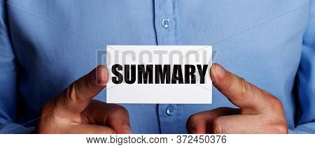 Summary Is Written On A White Business Card, Who Holds A Man In A Blue Shirt With His Hands.