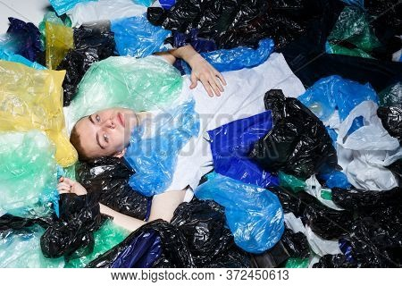 Horizontal View. Young Man With Blue Eyes, Lying Down, With Ring In Nose, Surrounded By Plastic Bags