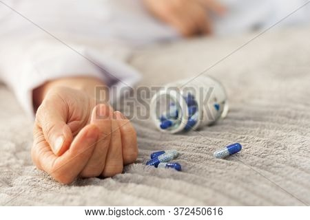 Woman's Hand Close Up Committing Suicide By Overdosing On Medication, Pills And Bottle Beside. Overd