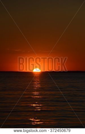 Bright Sunset Over The Lake. Sunny Path In Calm Water. Red-orange Sunset. Dark Water. The Sun Sets O