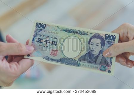 Close Up Of Hand Paying Or Giving Cash Money Japanese Yen Banknote To Another To Person. The Yen Is