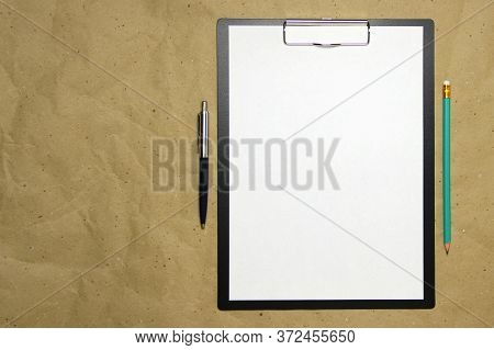 A Tablet With A White Sheet With Pen And Pencil On A Beige Craft Paper. Concept Of New Opportunities