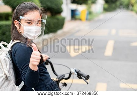 Back To School. Asian Child Girl Wearing Face Mask And Giving Thumb Up With Backpack Biking A Bicycl