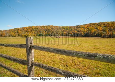 From American Country Road A Rural Landscape With Farmhouse In Distance Beyond Rustic Post And Rail