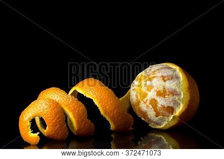 Half Peeled Orange On A Black Background. The Peel Lies Nearby. Tropical Fruit.