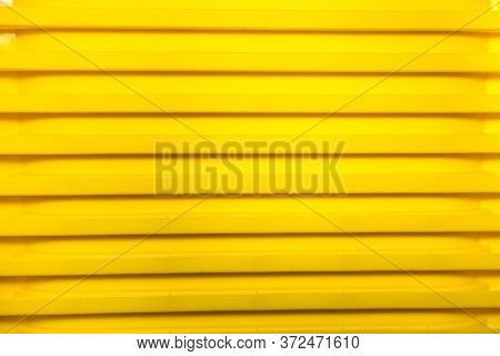 Vertical Bright Stripes Of Plastic Basins Stacked In A Pile Of Yellow. Abstraction, Structures, Desi