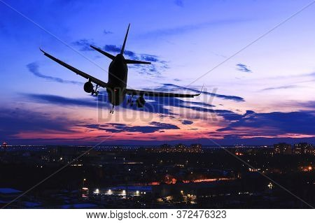 Plane Landing In Night City. Steep Turn Of Jet Airplane Over Town At Sunset. Silhouette Of Aircraft.
